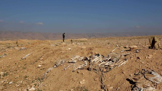 Bones, suspected to belong to Iraq's Yazidi community, are seen in a mass grave on the outskirts of the town of Sinjar