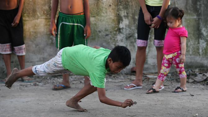 A Filipino boy reaches out to hit his opponents coins during a game which they call Pastra in suburban Malabon, Philippines on Sunday, Aug. 24, 2014. Players try to knock out coins inside a square marked on the ground or hit his opponent's coins to win. Winner gets all the coins in the box. (AP Photo/Aaron Favila)