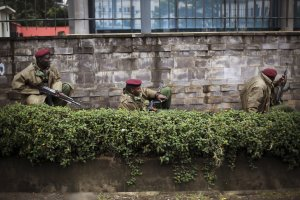 Kenya security forces are seen behind a wall outside …