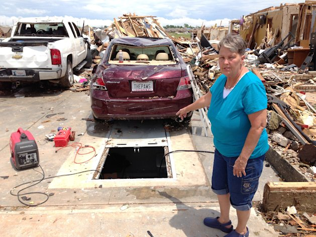 <p> On Thursday, May 23, 2013 Sherry Wells stands near the storm shelter where she took cover when a tornado destroyed her home on Monday May 20, 2013 in Moore, Okla. Wells said she and her husband won a lottery draw to receive a government-subsidized rebate to install the storm shelter. A contractor finished work on the concrete bunker beneath the slab of their garage about three weeks before the tornado hit. (AP Photo/David A. Lieb)