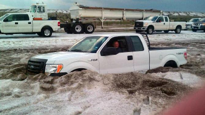 """In this Wednesday, April 11, 2012 photo provided by the Amarillo/Potter/Randall Office of Emergency Management a motorist sits in a truck partially buried in slushy hail near Amarillo, Texas. Weather service crews are assessing the damage from a Texas Panhandle storm that dumped several feet of nickel-sized hail, stranded motorists in muddy, hail drifts and closed a highway for several hours. National Weather Service Meteorologist Justyn Jackson said Thursday that hail that fell amid a rainstorm the day before was real small but """"there was a lot of it"""" in a concentrated area, accumulating 2- to 4-feet deep. (AP Photo/Courtesy of Amarillo/Potter/Randall Office of Emergency Management)"""