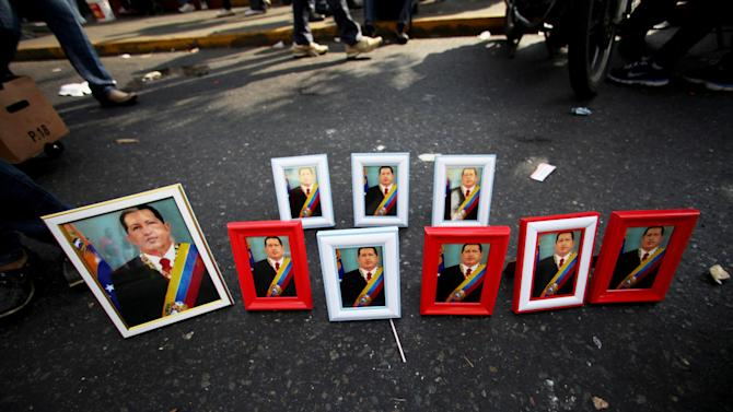 Portraits of Venezuela's President Hugo Chavez sit for sale along a street on the sidelines of a rally in Caracas, Venezuela, Wednesday, Jan. 23, 2013. Many credit Chavez with easing their poverty and expanding public services. To them, it does not matter that Venezuela suffers from 20 percent inflation, that the oil-producing nation is often short on cooking oil and sugar, that it has one of the world's highest murder rates, and that the president will not divulge the details of his cancer.  (AP Photo/Fernando Llano)