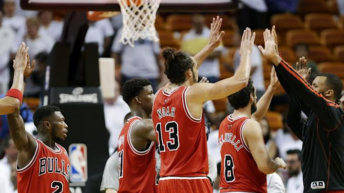Chicago Bulls' Nate Robinson (2) and Joakim Noah (13) celebrate with their teammates after defeating the Miami Heat 93-86 in Game 1 of their NBA basketball playoff series in the Eastern Conference semifinals, Monday, May 6, 2013, in Miami. (AP Photo/Lynne Sladky)