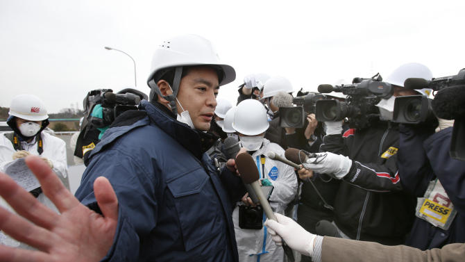 In this photo taken Friday, March 1, 2013, Senior Vice-Minister of Environment Shinji Inoue answers a reporter's question after inspecting workers's decontamination operation at the entrance of the Joban Expressway in Tomioka, Fukushima prefecture inside the exclusion zone surrounding the Fukushima Dai-ichi nuclear plant in Japan. Two years after the triple calamities of earthquake, tsunami and nuclear disaster ravaged Japan's northeastern Pacific coast, radioactive and chemical contamination remains a threat as clean-up projects face troubles with organized crime and mishandling.   (AP Photo/Shizuo Kambayashi)