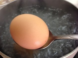Placing the eggs in water with a spoon to avoid breaking them