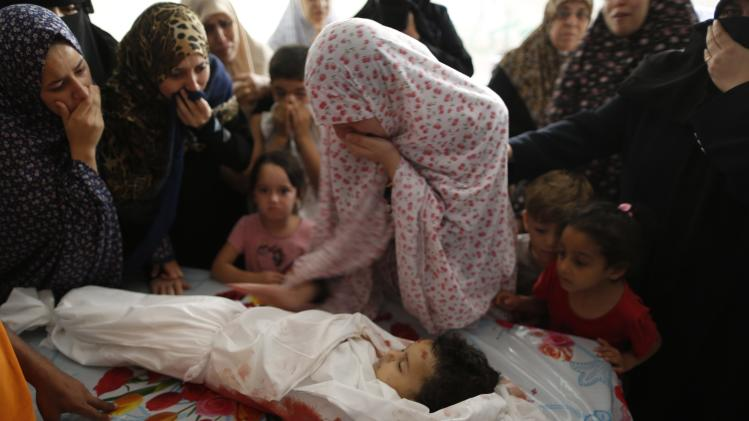 The mother of Palestinian girl, whom medics said was killed in an Israeli air strike, mourns next to her body during her funeral in Gaza City