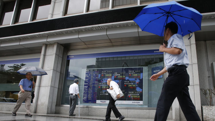 People walk by an electronic stock indicator in Tokyo Monday, Aug. 6, 2012. Asian stock markets rose sharply in early trading Monday, boosted by stronger-than-expected U.S. hiring figures for July following three months of weak job gains. (AP Photo/Shizuo Kambayashi)