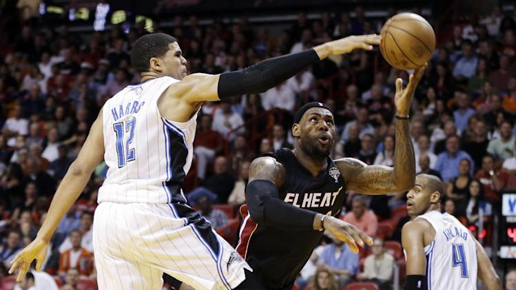 Orlando Magic's Tobias Harris (12) blocks a shot by Miami Heat's LeBron James (6) during the first quarter of an NBA basketball game in Miami, Wednesday, March 6, 2013. (AP Photo/J Pat Carter)