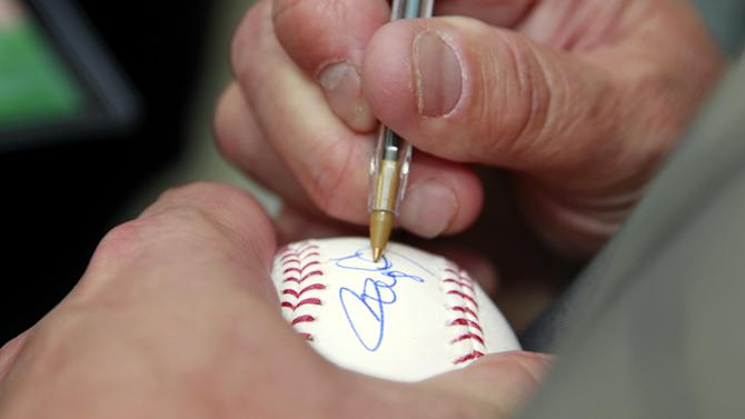 Former Major League Baseball pitcher Roger Clemens autographs as baseball as he leaves federal court, Thursday, May 17, 2012, in Washington. (AP Photo/Haraz N. Ghanbari)