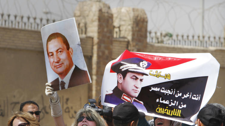 "Egyptian pro-Mubarak supporters shout slogans and hold posters showing former Egyptian President Hosni Mubarak, outside a court in Cairo, Egypt, Saturday, May 11, 2013. Egyptian prosecutors say they are presenting new evidence in the retrial of former President Hosni Mubarak for failing to stop the killing of 900 protestors in the 2011 unrest that ousted him. Arabic writing on poster reads, ""you are the last of the Egyptian historical leaders."" (AP Photo/ Amr Nabil)"