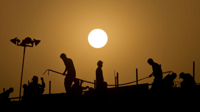Pakistanis work at the construction site of an overhead bridge at sunset in Islamabad, Pakistan, Sunday, July 5, 2015. (AP Photo/Anjum Naveed)