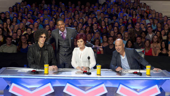 """In this April 2012 photo released by NBC, host Nick Cannon, standing, poses with judges, seated from left, Howard Stern, Sharon Osbourne and Howie Mandel from the talent competition series """"America's Got Talent,"""" during auditions in Tampa, Fla. A prime-time display of artistic and athletic talent has carried NBC to the top of the television ratings. The Nielsen company says NBC was last week's most popular network. Three editions of """"America's Got Talent"""" on Monday, Tuesday and Wednesday, June 25-27, were the three most-watched shows.  (AP Photo/NBC, Virginia Sherwood)"""