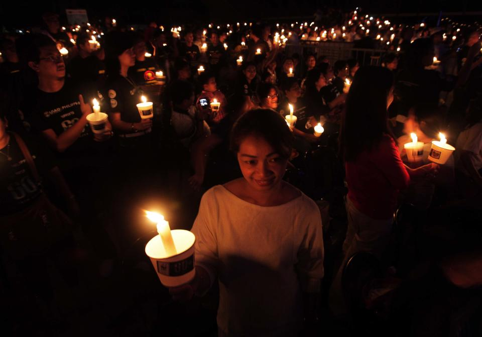 Participants hold lighted candle after the switching off of lights in observance of Earth Hour Saturday, March 31, 2012, in Manila's financial district of Makati, Philippines. The switching off of lights for one hour is being observed world-wide as part of a global effort to shine a spotlight on climate change. (AP Photo/Pat Roque)