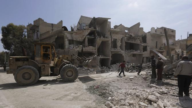 Residents inspect damage at a site hit by what activists said was a barrel bomb dropped by warplanes operated by forces of Syria's President Assad in Aleppo