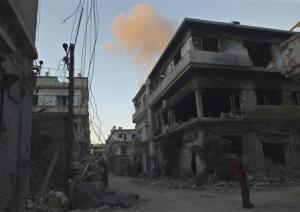 A man stands in front of buildings damaged by what activists said was shelling by forces loyal to Syria's President Bashar al-Assad, as smoke rises in the background in the besieged area of Homs
