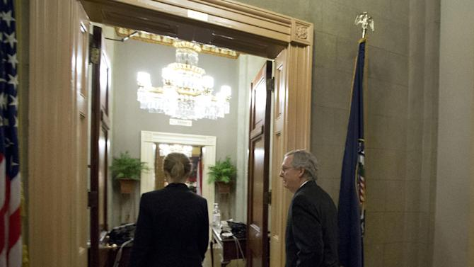 Senate Minority Leader Mitch McConnell, right, from Kentucky, heads into his office after a vote on the fiscal cliff, on Capitol Hill Tuesday, Jan. 1, 2013 in Washington. The Senate passed legislation early New Year's Day to neutralize a fiscal cliff combination of across-the-board tax increases and spending cuts that kicked in at midnight. (AP Photo/Alex Brandon)