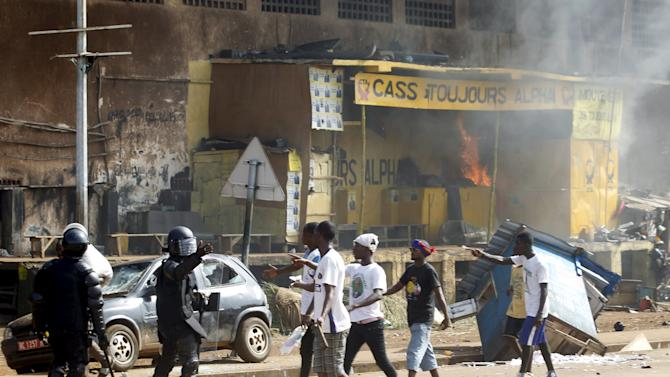 Supporters of former PM and UFDG presidential candidate Diallo complain to security forces during a confrontation with supporters of Guinea's President and RPG leader Conde during an UFDG electoral rally in Conakry