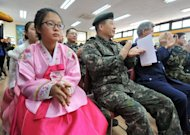 South Korean graduates wearing traditional dress sit next to military officers during a graduation ceremony for Taesungdong Elementary School at Taesungdong freedom village near the border village of Panmunjom in Paju on February 15, 2013. Six students graduated from the only school in this South Korean village sitting inside the demilitarized zone between North and South Korea