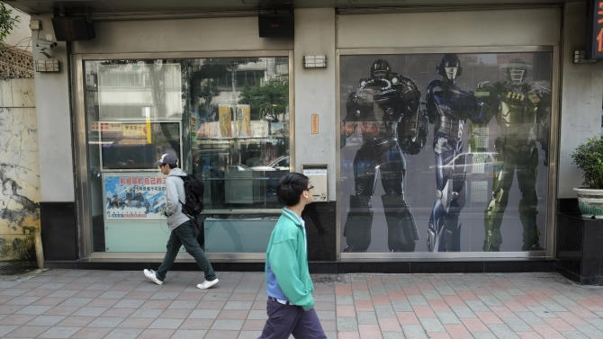 """In this March 22, 2013 photo, young men pass a military recruitment center using """"Transformer"""" robots to attract young Taiwanese to volunteer in Taipei, Taiwan. A Taiwanese plan to end mandatory military service and shift to an all-volunteer force is running into a problem: Not enough volunteers. Such forces are generally considered superior to conscripted ones, because those serving want to be there. Recruitment is proving difficult in a prosperous society that offers young people alternatives and doesn't glorify military service.  (AP Photo/Wally Santana)"""