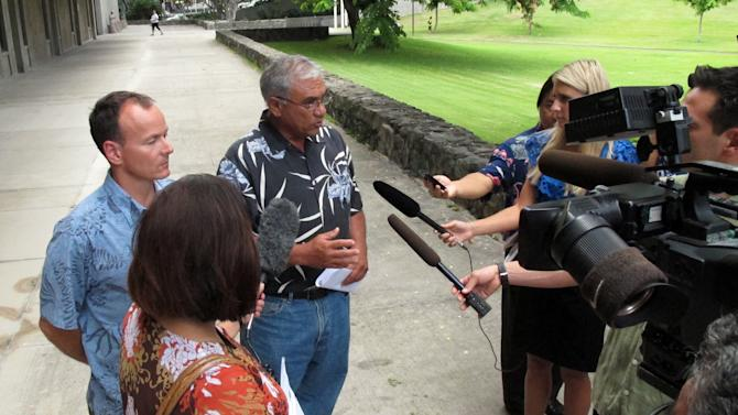 Chairman William Aila of the Hawaii Department of Land and Natural Resources, center, speaks to reporters at a news conference in Honolulu on Tuesday, Aug. 20, 2013. Hawaii officials plan to spend the next two years studying tiger shark movements around Maui amid what they call an unprecedented spike in overall shark attacks since the start of 2012. (AP Photo/Oskar Garcia)