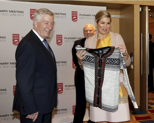 Dutch Queen Maxima holds a traditional Norwegian knitted jacket, which was presented to her, as she arrived for the plenary session of the FATF in Oslo