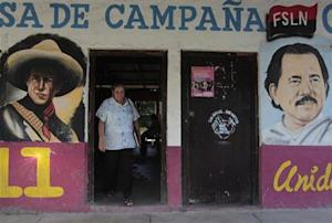 A woman walks past murals of Nicaragua's President Daniel Ortega and Nicaraguan revolutionary and Sandinista leader Augusto Cesar Sandino in Catarina