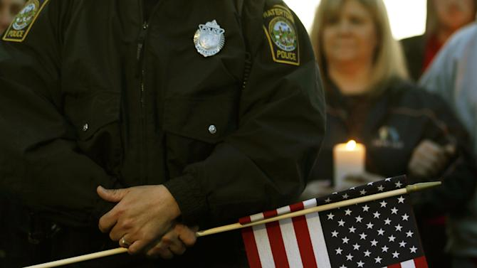 Watertown Police officer Brandon O'Neill holds a flag during a vigil for the victims of the Boston Marathon bombing, Saturday, April 20, 2013, in Watertown, Mass. Suspected bomber Dzhokhar Tsarnaev is hospitalized in serious condition with unspecified injuries after he was captured in an all day manhunt the day before. (AP Photo/Julio Cortez)
