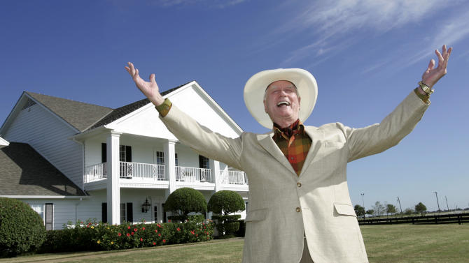"""FILE - In this Oct. 9, 2008 file photo, actor Larry Hagman poses in front of the Southfork Ranch mansion in Parker, Texas made famous in the television show """"Dallas.""""  Actor Larry Hagman, who for more than a decade played villainous patriarch JR Ewing in the TV soap Dallas, has died at the age of 81, his family said Saturday Nov. 24, 2012.  (AP Photo/Tony Gutierrez, File)"""