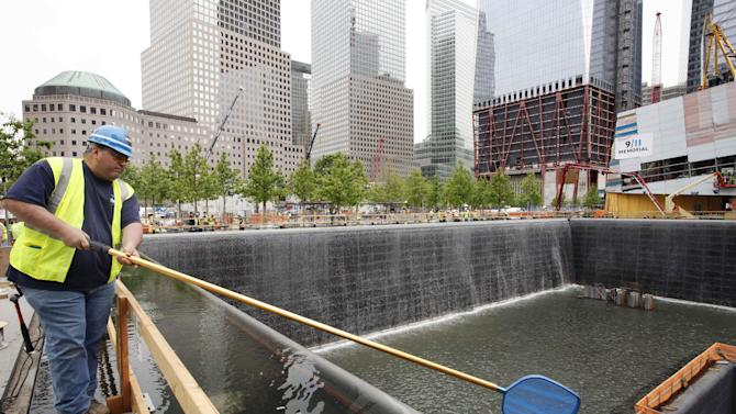 FILE - In this May 13, 2011 file photo, Anthony St. Jeanos, left, uses a net to skim debris from the water during a test of the waterfalls at the National September 11 Memorial, at the World Trade Center site in New York. The foundation that runs the memorial estimates that once the roughly $700 million project is complete, it will cost $60 million a year to operate. (AP Photo/Mark Lennihan, File)