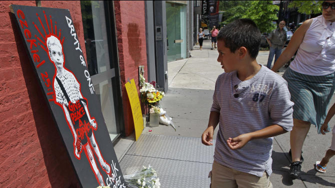 A boy stops to look at a makeshift memorial to Etan Patz, who was six when he disappeared in 1979, in New York, Sunday, May 27, 2012. The memorial sprung up at the site where, according to police, suspect Pedro Hernandez, now 51, claims the murder took place. The metal sidewalk doors lead to a basement where Hernandez, who was 18 at the time and an employee of a bodega, said he murdered the boy. (AP Photo/Kathy Willens)