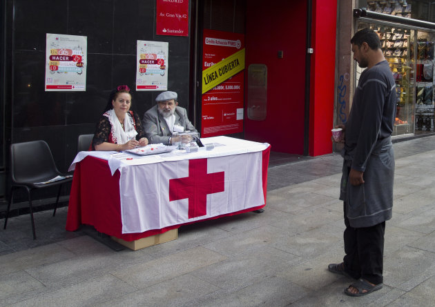 A man begging with a paper cup stands looking at Red Cross volunteers collecting money in the street, in Madrid, Wednesday Oct. 10, 2012. Spain's Red Cross is launching its first-ever public appeal for donations to help the growing number of Spaniards in need of help because of the economic crisis.Spokesman Miguel Angel Rodriguez said Tuesday the agency is looking to round up some euro 30 million ($38.87 million) over the next two years to help an extra 300,000 people. (AP Photo/Paul White)