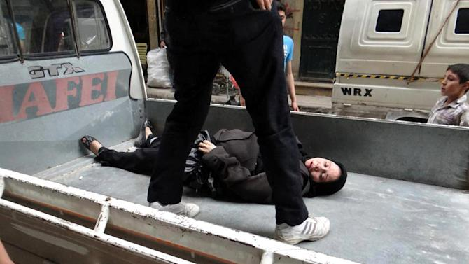 This citizen journalism image provided by Aleppo Revolution Against Assad's Regime, which has been authenticated based on its contents and other AP reporting, shows a Syrian man putting an injured woman into a car after being shot by a Syrian Army sniper, in the neighborhood of Bustan Al-Qasr in Aleppo, Syria, Thursday, April. 11, 2013. (AP Photo/Aleppo Revolution Against Assad's Regime)