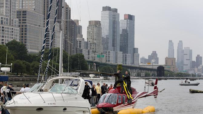 A helicopter rests on a pontoon at the 79th Street Boat Basin after emergency landing over the Hudson river, Sunday, June 30, 2013, in New York. New York authorities say a helicopter carrying four Swedish tourists landed in the Hudson River off Manhattan Sunday, but everyone has been rescued. (AP Photo/John Minchillo)