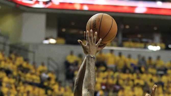 Miami Heat's Dwyane Wade (3) shoots over Indiana Pacers' Paul George during the first half of Game 3 of their NBA basketball Eastern Conference semifinal playoff series, Thursday, May 17, 2012, in Indianapolis. (AP Photo/Darron Cummings)