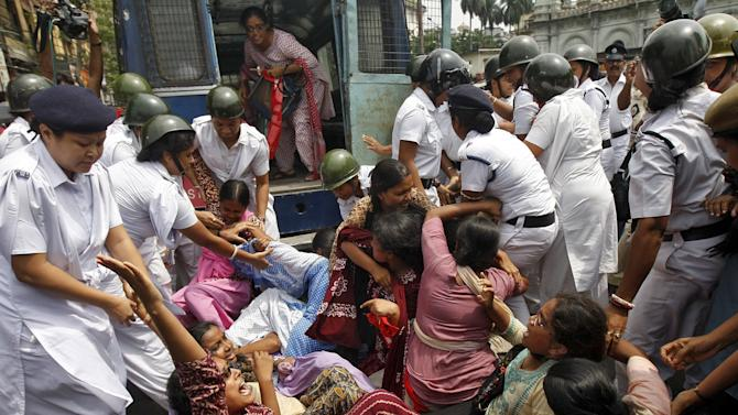 Policewomen try to detain activists from SUCI during a nationwide strike in Kolkata