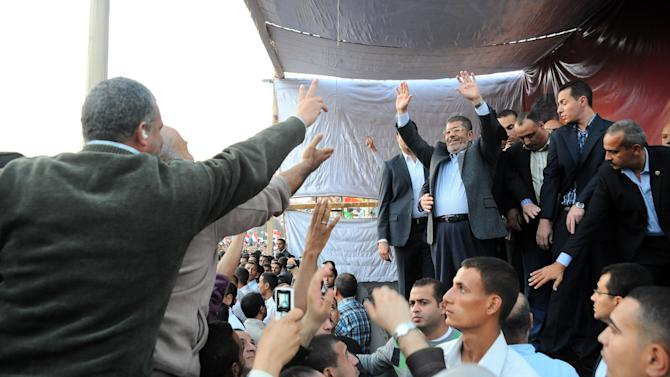 "In this Friday, Nov. 23, 2012 photo released by the Egyptian Presidency, President Mohammed Morsi, center right, waves to supporters outside the Presidential palace in Cairo, Egypt.  Egypt's official news agency says that the country's highest body of judges has called the president's recent decrees an ""unprecedented assault on the independence of the judiciary and its rulings."" In a statement carried on MEAN Saturday, the Supreme Judicial Council says they regret the declarations President Mohammed Morsi issued Thursday.(AP Photo/Egyptian Presidency)"