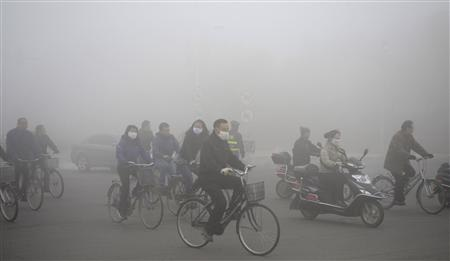 People ride along a street on a smoggy day in Daqing, Heilongjiang province, October 21, 2013. REUTERS/Stringer