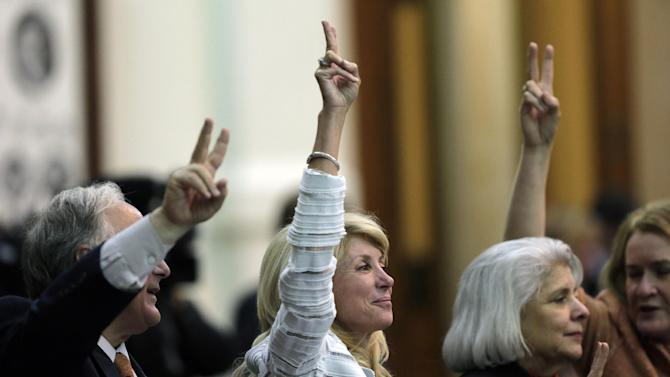 """FILE - In this Tuesday, June 25, 2013, file photo, Sen. Wendy Davis, D-Fort Worth, center, holds up two fingers to signal a """"No"""" vote as the session where tshe tried to filibuster an abortion bill draws to a close, in Austin, Texas. Hundreds of abortion rights activists ensured that the first special legislative session descended into chaos. Now, Texas Gov. Rick Perry has convened a second one and urged abortion opponents to respond with mobilizations of their own. (AP Photo/Eric Gay, File)"""