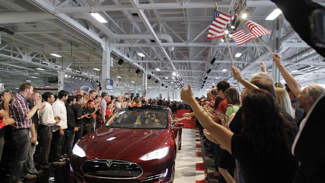 FILE - In this June 22, 2012 file photo, Tesla workers cheer on one the first Tesla Model S cars sold during a rally at the Tesla factory in Fremont, Calif. A healthier economy and more new model introductions should push U.S. auto sales above the 15 million mark in 2013, predicts an auto industry research firm. The Polk research firm says auto sales should continue to lead the country's economic recovery, rising nearly 7 percent over 2012 to 15.3 million new vehicle registrations. (AP Photo/Paul Sakuma, File)