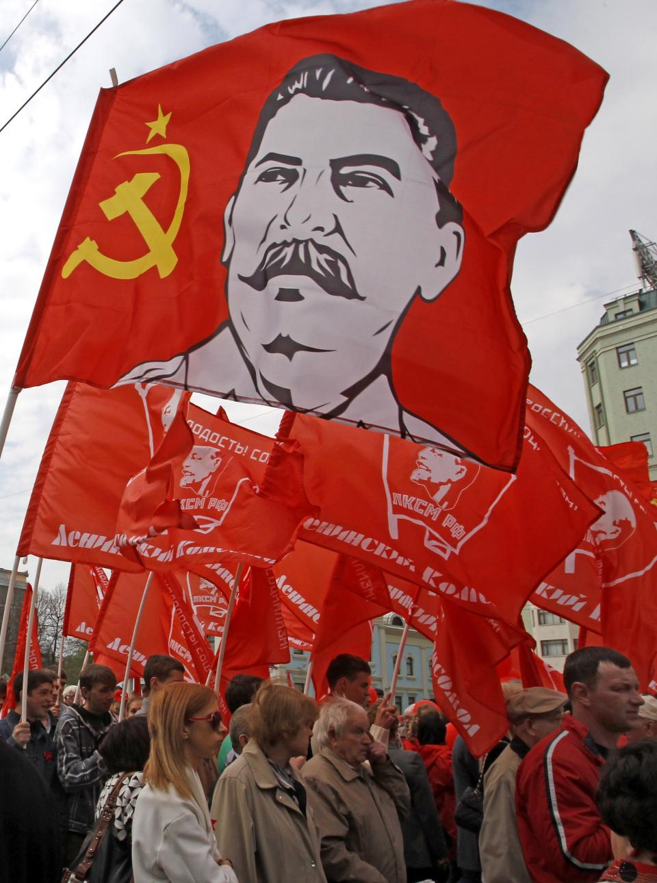 Communist Party supporters march with their flags during a rally to mark May Day in Moscow, Russia, Tuesday, May 1, 2012. Above is a flag with a a portrait of Soviet dictator Josef Stalin . (AP Photo/Mikhail Metzel)