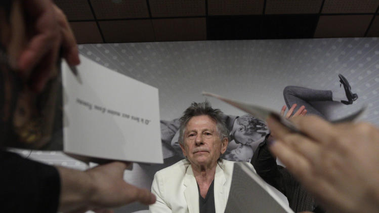 Director Roman Polanski signs autographs during a press conference for Venus in Fur at the 66th international film festival, in Cannes, southern France, Saturday, May 25, 2013. (AP Photo/Virginia Mayo)