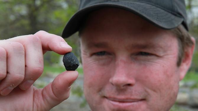 "Robert Ward displays one of two pieces of a meteorite he found at a park in Lotus, Calif., Wednesday, April 25, 2012.  Ward found the pieces from a meteor that was probably about the size of a minivan  when it entered the Earth's  atmosphere with a loud boom about 8 a.m. Sunday. The rocks came from a meteor, believed to between 4 to 5 billion years old.  Ward, who has been hunting and collecting meteorites for more than 20 years, said they are believed to be ""one of the oldest things known to man and one of the rarest types of meteorites there is."" (AP Photo/Rich Pedroncelli)"