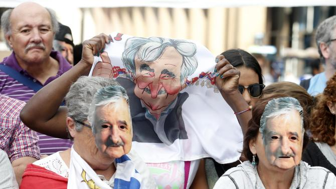 People wearing masks depicting Uruguay's President Jose Mujica participate in a ceremony where Mujica will receive the Uruguayan flag on the last working day of his term in Montevideo