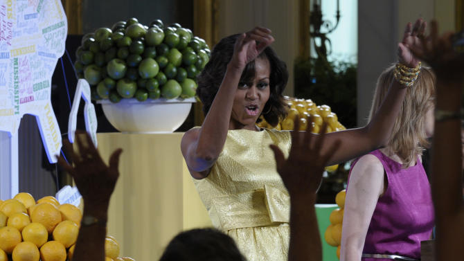 """First lady Michelle Obama is welcomed to speak at the second annual White House """"Kids' State Dinner"""" in the East Room of the White House in Washington, Tuesday, July 9, 2013. Mrs. Obama welcomed 54 children to the White House for creating winning recipes as part of a healthy lunch contest. (AP Photo/Susan Walsh)"""