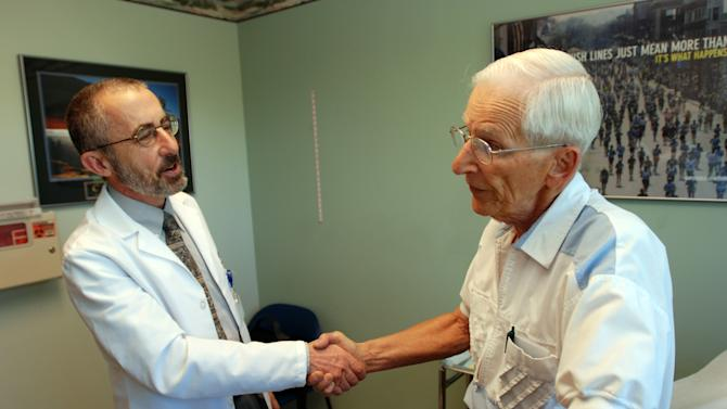 In this June 19, 2012 photo, Dr. Bruce Stowell shakes hands with patient Robert Busch at his office in Grants Pass, Ore. Stowell is among many doctors in rural areas who have capped the numbers of Medicare patients they take due to low reimbursement levels. A nationwide shortage of primary care physicians willing to set up practice in rural areas is making the problem worse. (AP Photo/Jeff Barnard)