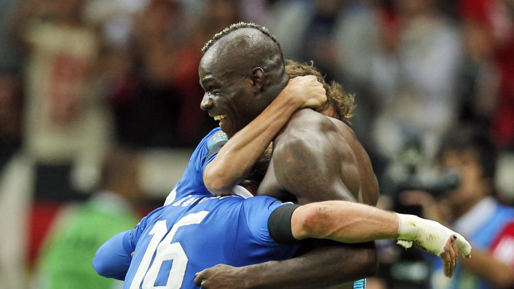 Italy's Mario Balotelli celebrates with teammates after scoring their second goal during the Euro 2012 soccer championship semifinal match between Germany and Italy in Warsaw, Poland, Thursday, June 28, 2012. (AP Photo/Michael Sohn)