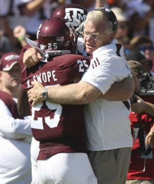 Texas A&M head coach Mike Sherman, right, celebrates with Ryan Swope, left, after Swope scored during the first half of an NCAA college football game against Baylor, Saturday, Oct. 15, 2011, in College Station, Texas. (AP Photo/Jon Eilts)