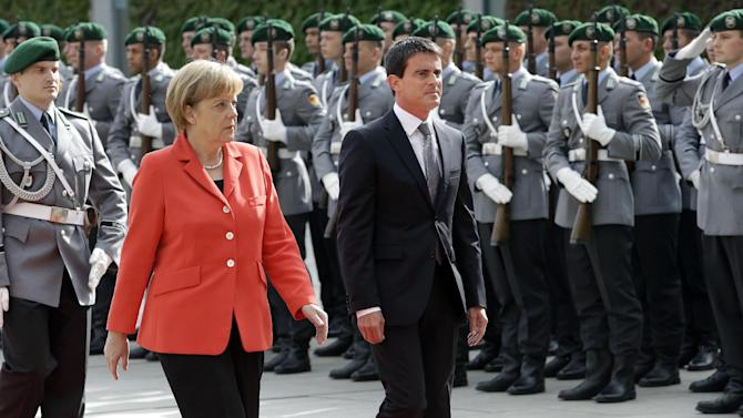 German Chancellor Angela Merkel, left, welcomes Prime Minister of France Manuel Valls, right, with military honors at the chancellery in Berlin, Germany, Monday, Sept. 22, 2014. (AP Photo/Michael Sohn)