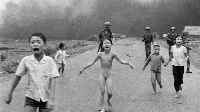 FILE - In this June 8, 1972 file photo, crying children, including 9-year-old Kim Phuc, center, run down Route 1 near Trang Bang, Vietnam after an aerial napalm attack on suspected Viet Cong hiding places as South Vietnamese forces from the 25th Division walk behind them. A South Vietnamese plane accidentally dropped its flaming napalm on South Vietnamese troops and civilians. From left, the children are Phan Thanh Tam, younger brother of Kim Phuc, who lost an eye, Phan Thanh Phouc, youngest brother of Kim Phuc, Kim Phuc, and Kim's cousins Ho Van Bon, and Ho Thi Ting. (AP Photo/Nick Ut, File)