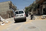 UN observers stop to speak to a man riding a bicycle in the damaged Bayyada district of the flashpoint Syrian city of Homs